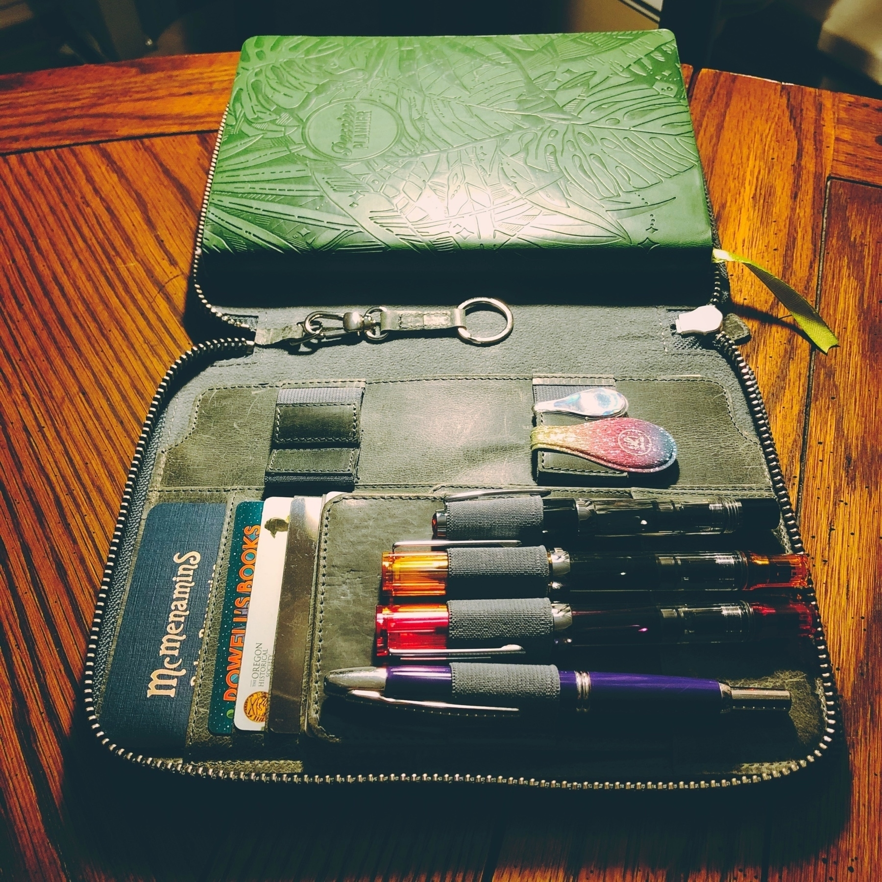 photo of a leather notebook cover, a Passion Planner, and four fountain pens