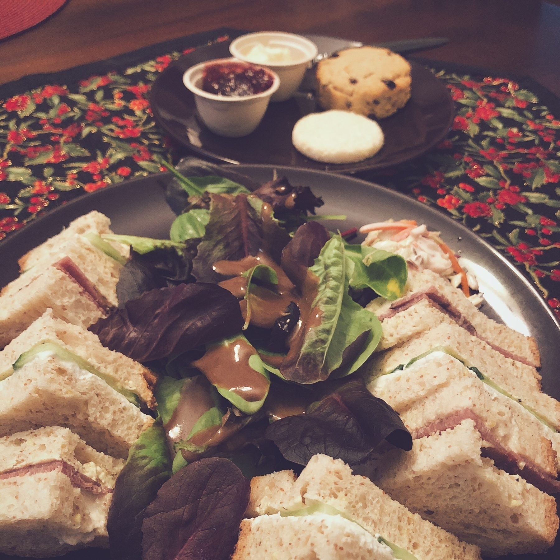 Plate of tea sandwiches and salad, with a smaller plate with a biscuit and scone in the background
