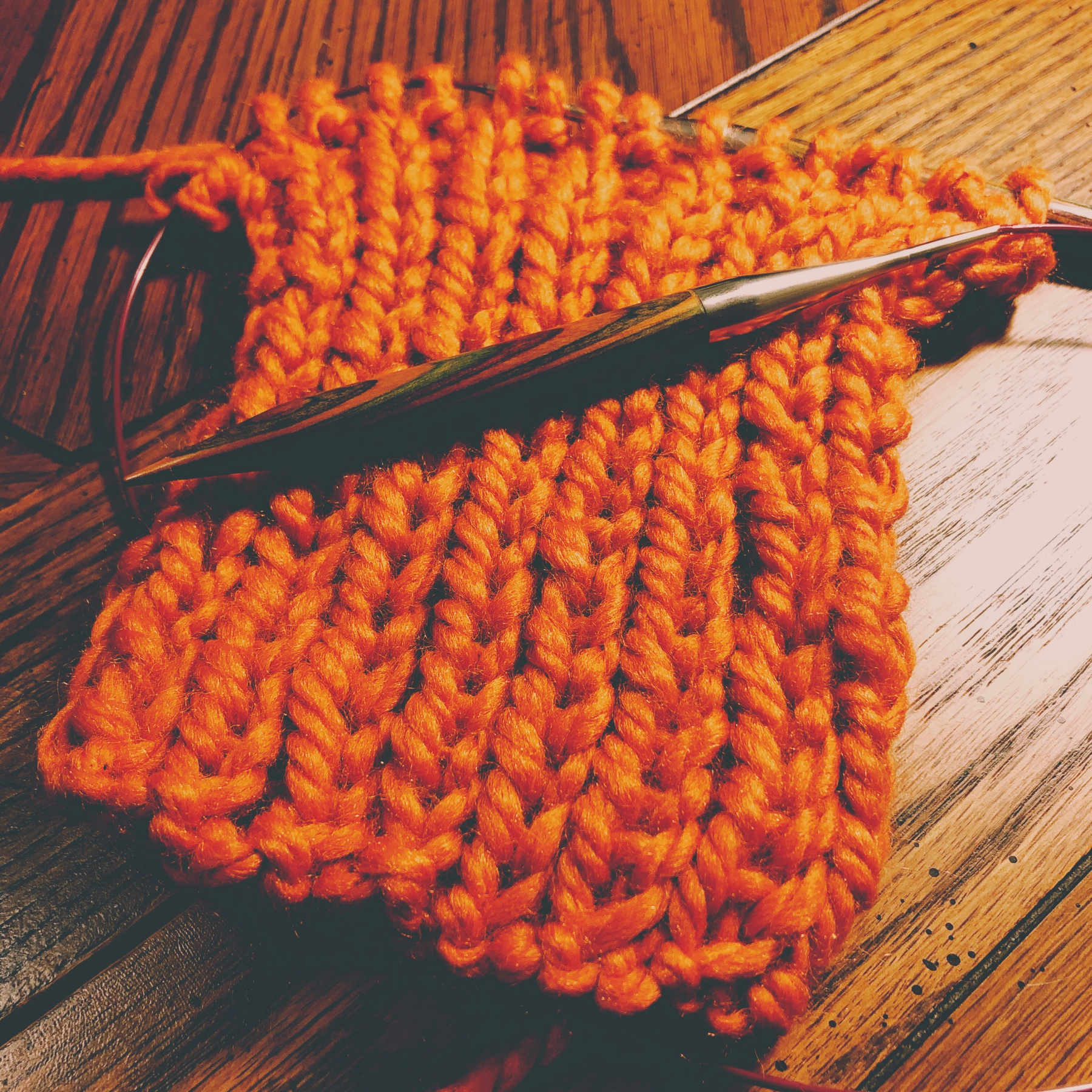 knitting project in progress, an orange rib knit scarf